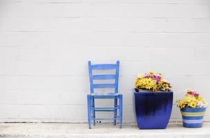 vit vägg blå stol och krukor