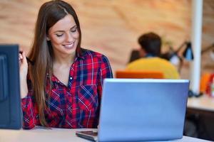 porträtt av affärskvinna leende medan du sitter vid kollegor i office foto