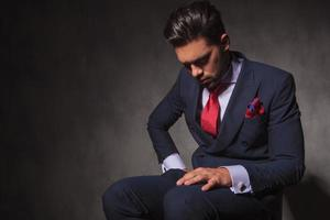 tankeväckande ung man som sitter på en stol foto