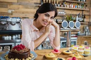 porträtt av servitris som lutar sig vid räknaren foto