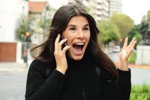 porträtt av en förvånad kvinna som pratar i smart telefon foto