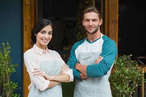 porträtt av leende servitör och servitris som står med korsade armar foto