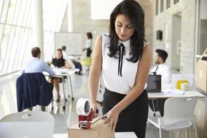 affärskvinna på kontoret förbereder paketet för frakt foto