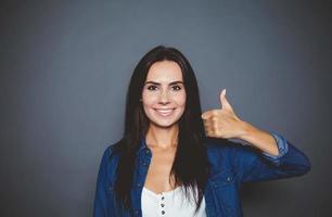 allt kommer att vara coolt. vacker le säker kvinna i en denimskjorta som visar ett handtecken ok på en isolerad grå bakgrund. foto
