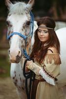 ung indisk flicka går med vit häst foto