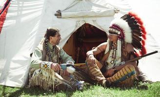 nordamerikanska indianer sitter vid en wigwam foto