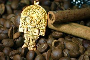 närbild av kaffebönor med guld indisk gud foto
