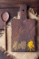 träskärbräda och sked med kryddor: kummin, bär, gurkmeja.