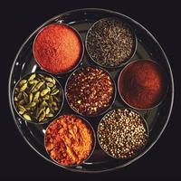 uppsättning indiska kryddor i metallskålar på svart bakgrund foto