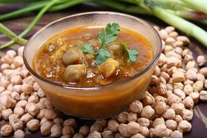 indisk kryddig chana masala med rå kikärter och grön lök foto