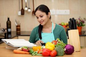 ung kvinna som läser en kockbok foto