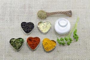 olika kryddor i hjärtformade behållare med salt och sked foto