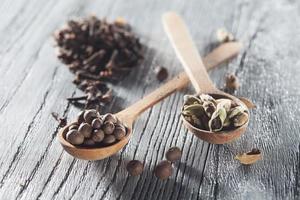 muskotnötter, kryddnejlika och kryddor i gammal sked på träbord foto