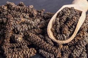 träskopa med lång peppar på mörk stenbakgrund foto