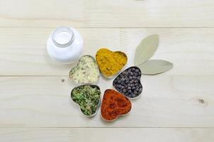 olika kryddor i hjärtformade behållare på ett bord foto