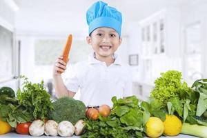 glad kockpojke med färska grönsaker foto