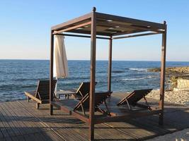 solstolar och paraply på sanden nära havet foto