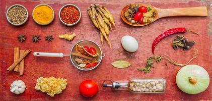 blandade kryddor och örter på röd bakgrund. foto
