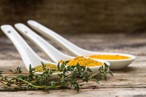 färska thymes med uppsättning kryddor på trä bakgrund foto