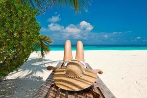 kvinna på stranden som ligger på schäslong foto