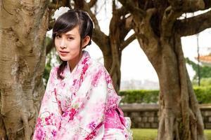 asiatisk kvinnakimono i trädgården foto