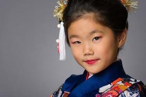 ung flicka i kimono på grått foto