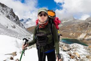 ung kvinna backpacker stående snö berg ovanför sjön. porträtt. foto