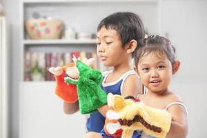 asiatiska syskon som spelar handdocka
