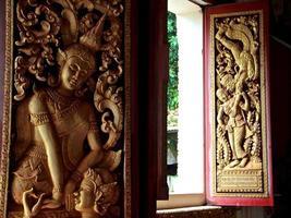 buddistiska träsniderier - vientiane, laos. foto