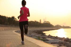 ung fitness kvinna kör på soluppgången vid havet foto