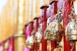 gyllene mässingsklocka som hänger på tempelstaketet
