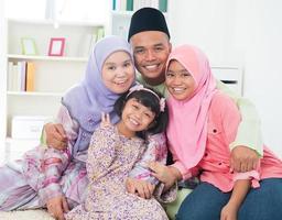 muslimska föräldrar som omfamnar sina två döttrar foto
