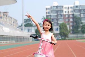asiatisk liten flicka och cykel foto