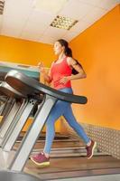 attraktiv asiatisk tjej kör på löpbandet foto