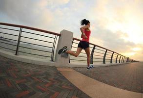 ung fitness kvinna löpare kör vid havet foto