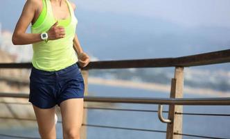 fitness sport kvinna kör på trä strandpromenaden foto