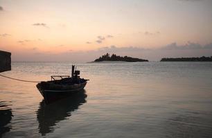 solnedgång - båt, hav och liten ö foto