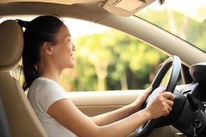 glad kvinna förare som kör sin bil foto