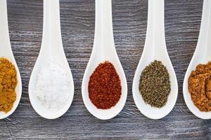 fem keramiska skedar med färgglada kryddor foto