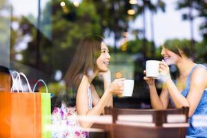 två ung kvinna som pratar i ett kafé foto
