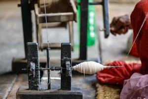 nepalesisk kvinna som snurrar bomull foto