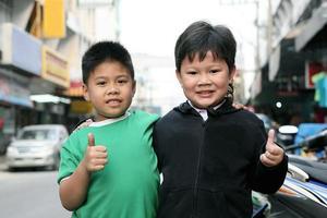två små pojkar som gör en tumme uppåt foto