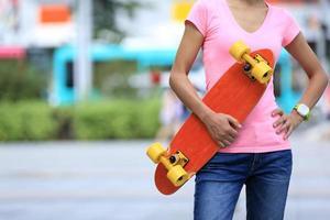 ung asiatisk kvinna skateboarder med skateboard på staden