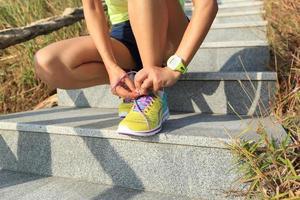 löpare för ung kvinna som knyter skosnören på stenspår foto