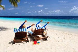 lyckliga par kopplar av på en tropisk strand foto