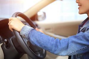 ung asiatisk kvinnoförare som kör bil foto