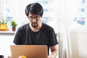 man som arbetar på laptop, hemma foto