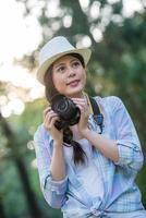vacker asiatisk flicka som ler med fotografering av digital kamera, foto