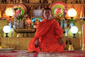 munk mediterar i lotusläget foto