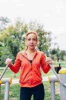 kvinna i fitnesskläder som gör övningar i parken foto